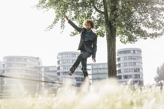 Young businessman balancing on slackline — Stock Photo