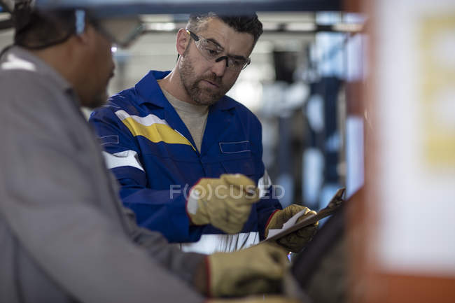 Two tire repairmen with clipboard in factory — Stock Photo
