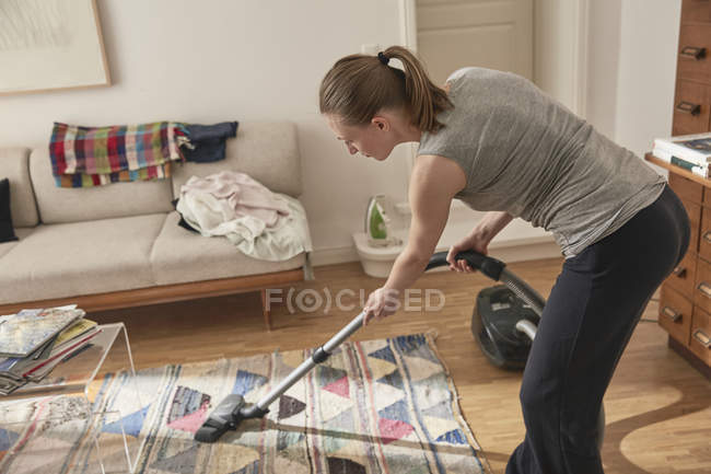 Woman vacuum cleaning at home — Stock Photo