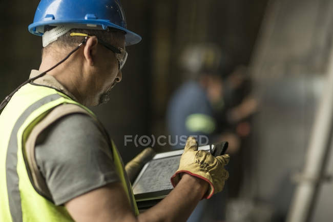 Engineer looking at blueprint on digital tablet — Stock Photo