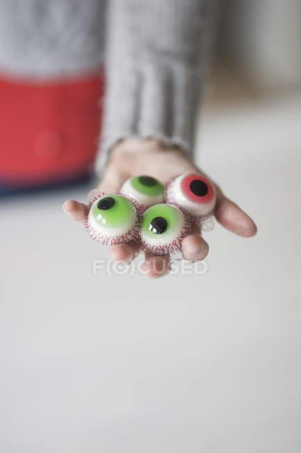 Mulher segurando doces artificiais olhos — Fotografia de Stock