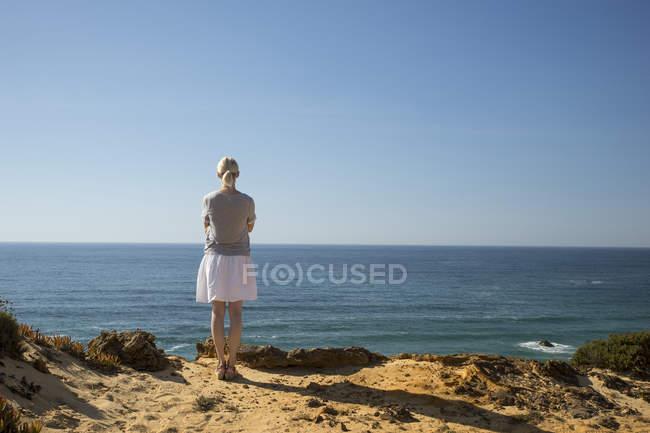 Женщина, стоя на берегу, глядя на расстоянии — стоковое фото