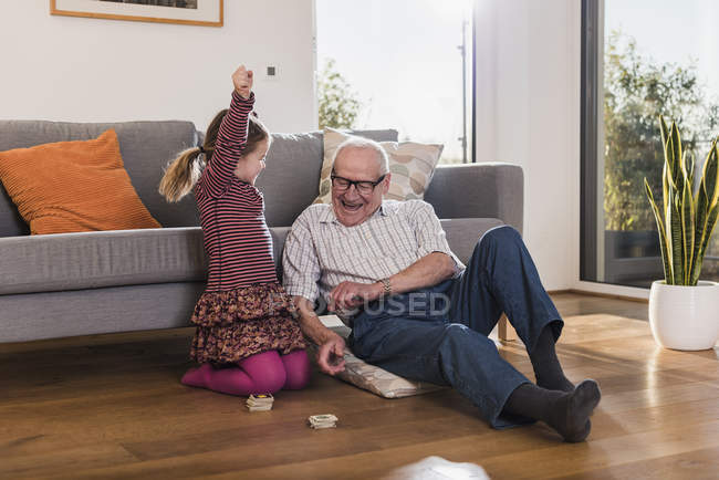 Grandfather and granddaughter playing memory, girl celebrating victory — Stock Photo