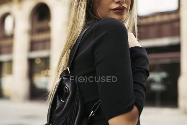 Giovane donna che porta borsa a tracolla in città — Foto stock