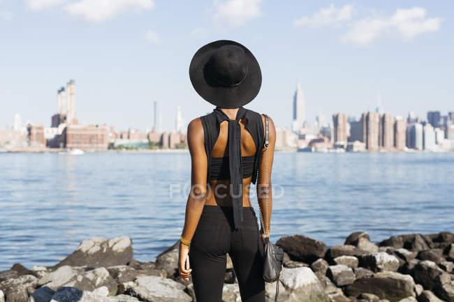 Giovane donna in piedi a East River, Brooklyn, New York, Stati Uniti — Foto stock