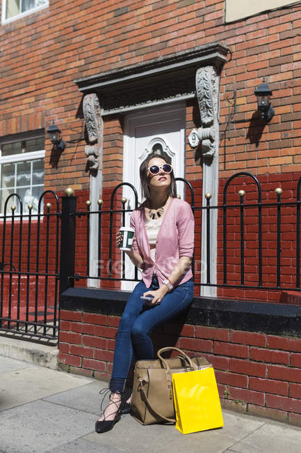 Young casual girl sitting on fence with bags and beverage — Stock Photo