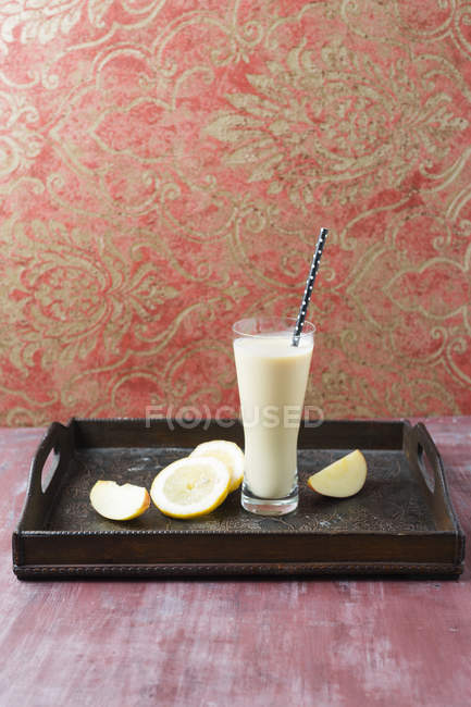 Glass of banana smoothie with apple and lemon on wooden board — Stock Photo