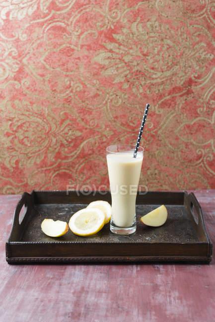 Vidro de batido de banana com maçã e limão na placa de madeira — Fotografia de Stock