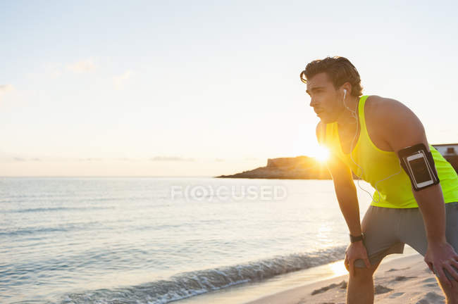 Young jogger having a break at beach at sunrise — Stock Photo