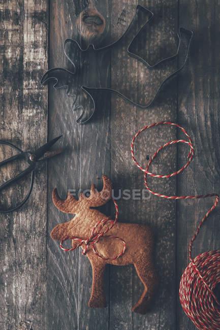 Galletas con forma de alce, cortador de la galleta, tijeras y cadena en madera oscura - foto de stock