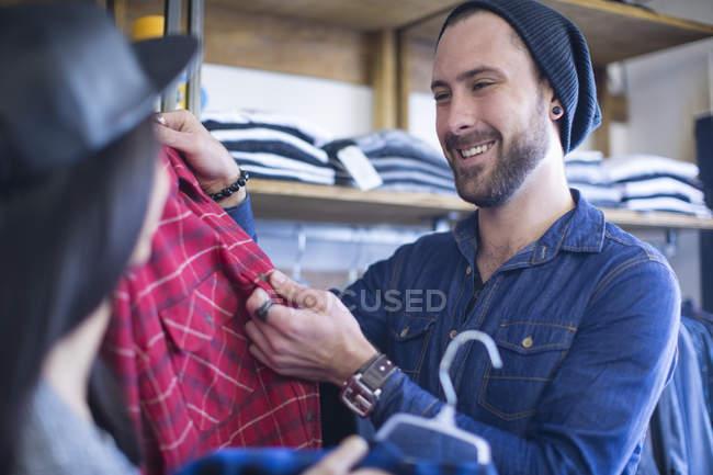Amici felici che scelgono i vestiti nel negozio — Foto stock