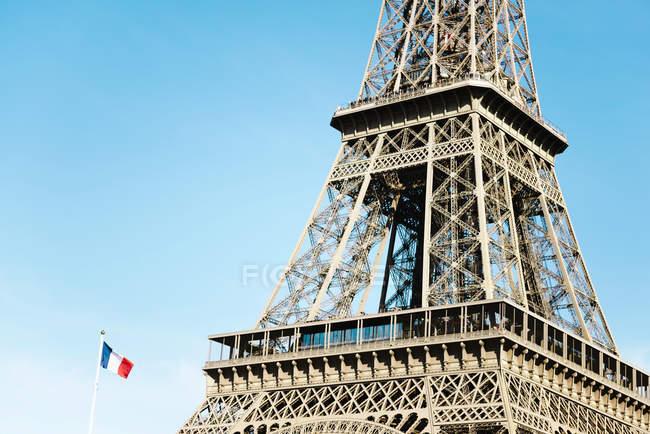 Parigi, Francia. Torre Eiffel e bandiera francese in una giornata di sole — Foto stock