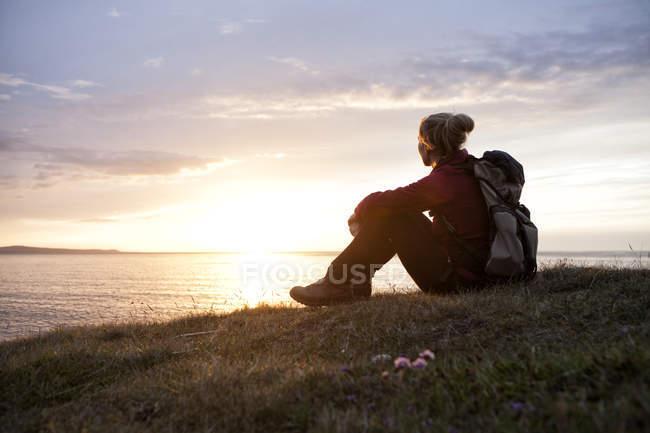Islande, randonneuse assise sur une prairie et regardant le crépuscule — Photo de stock