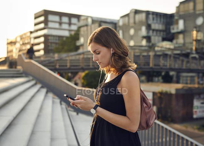 Alemanha, Hamburgo, Jovem com telefone inteligente explorando Hamburgo — Fotografia de Stock