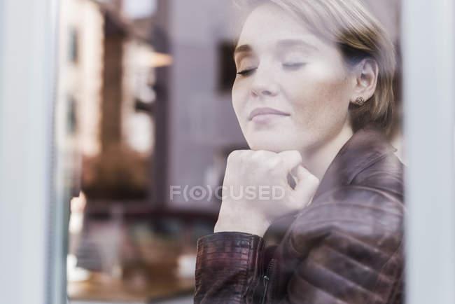 Jeune femme avec les yeux fermés derrière la vitre — Photo de stock