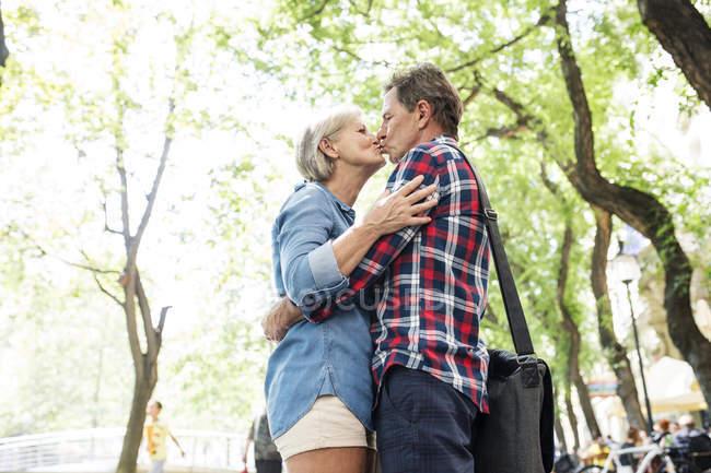 Glücklich süß senior pärchen umarmen und küssen im park — Stockfoto