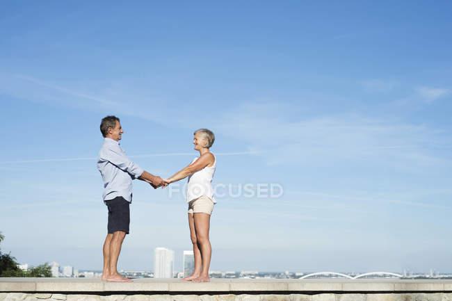 Felice coppia anziana in piedi a piedi nudi su un muro di fronte al cielo tenendosi per mano — Foto stock
