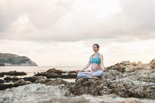 Donna incinta che pratica yoga in mare — Foto stock