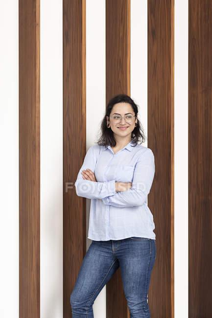 Sorrindo jovem mulher na frente da parede de madeira — Fotografia de Stock
