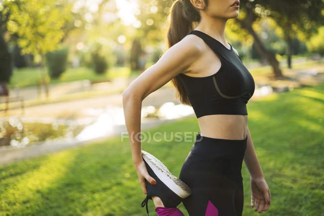 Спортивная молодая женщина, растянувшаяся в парке на закате — стоковое фото