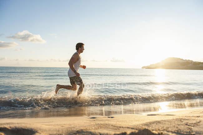 Jovem, movimentando-se na praia de manhã — Fotografia de Stock