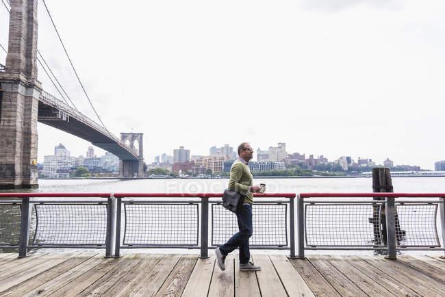 USA, New York City, homme marchant à East River avec café à emporter — Photo de stock