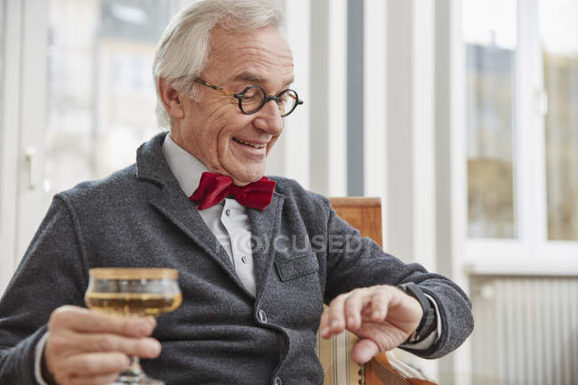 Smiling senior man sitting on chair holding champagne glass looking on smartwatch — Stock Photo