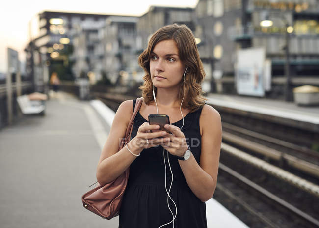 Germany, Young woman with smart phone exploring Hamburg — Stock Photo