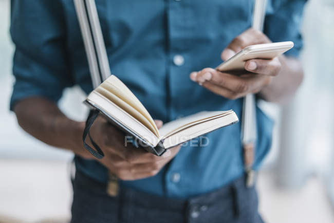 Junger Mann mit Smartphone und Notebook holding — Stockfoto