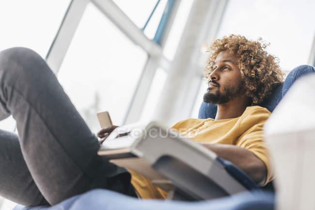 Молодой человек Холдинг смартфон и глядя на расстоянии — стоковое фото