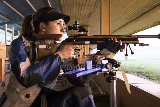 Женщина со спортивной винтовкой в тире — стоковое фото