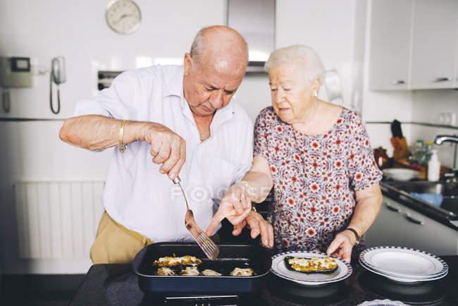 Senior couple serving stuffed eggplants in the kitchen — Stock Photo