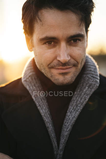 Portrait of man with stubble standing at sunset — Stock Photo