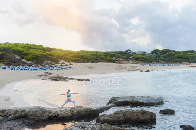 Donna incinta che pratica yoga sulla costa rocciosa — Foto stock