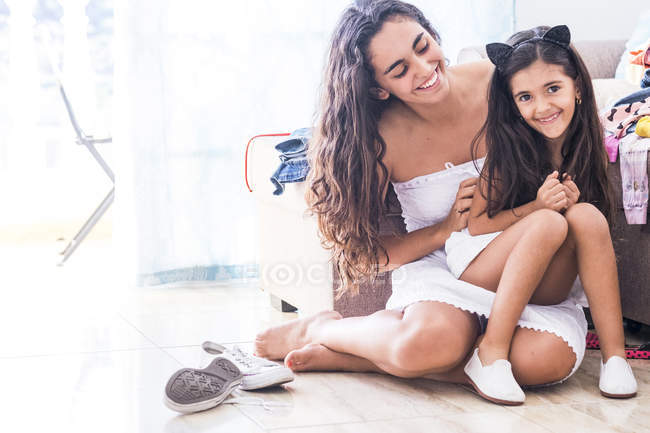Teenage girl and her little sister at home — Stock Photo