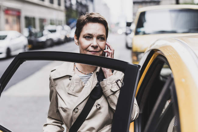 Woman on cell phone entering a taxi in Manhattan, New York City, USA — Stock Photo