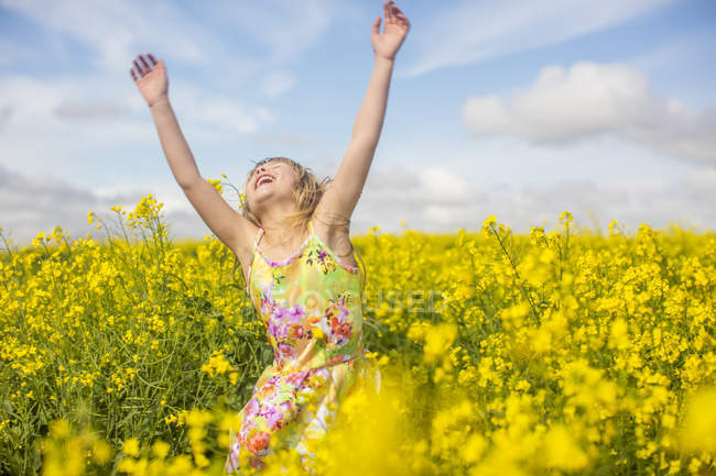 Little girl dancing in rape field — Stock Photo