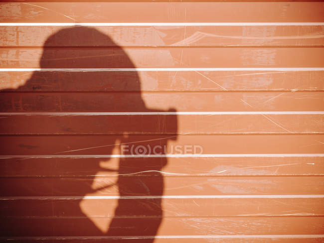Shadow of a man taking picture with camera on a wall — Stock Photo