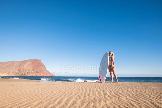 Молоді жінки серфер Іспанії, Тенеріфе, стоячи на піщаному пляжі — стокове фото