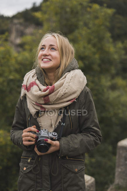 Smiling young woman with camera outdoors — Stock Photo