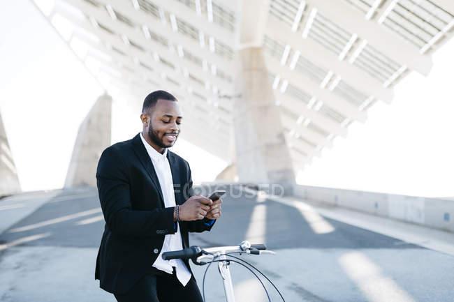 Бизнесмен на велосипеде с помощью мобильного телефона — стоковое фото