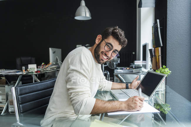 Portrait of smiling young man working with laptop at desk in a modern office — Stock Photo