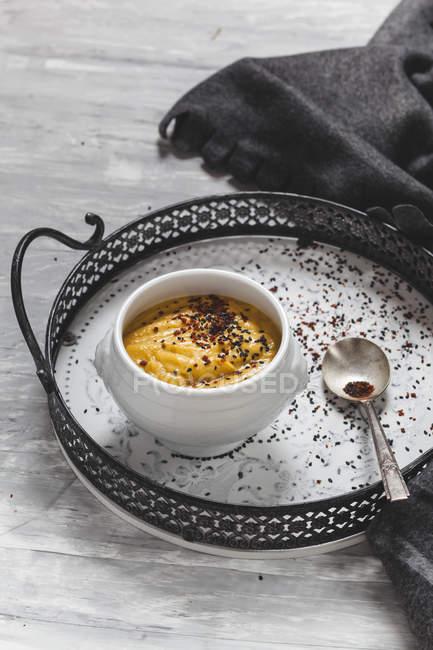 Kürbissuppe mit schwarzem Sesam und Chili Flocken auf Tablett — Stockfoto
