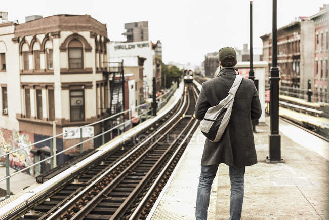 Young man waiting for metro at train station platform — Stock Photo