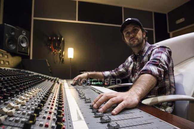 Человек, работающий в комнате управления студии звукозаписи — стоковое фото