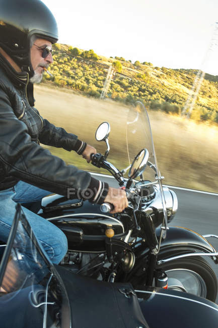 Biker wearing helmet driving sidecar motorcycle — Stock Photo