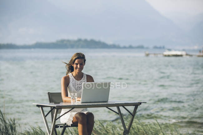 Italy, Lake Garda, young woman sitting at table with laptop — Stock Photo