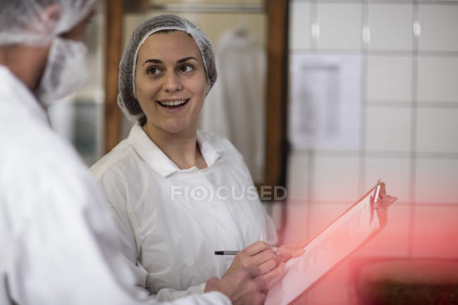 Cheese factory workers talking at work — Stock Photo