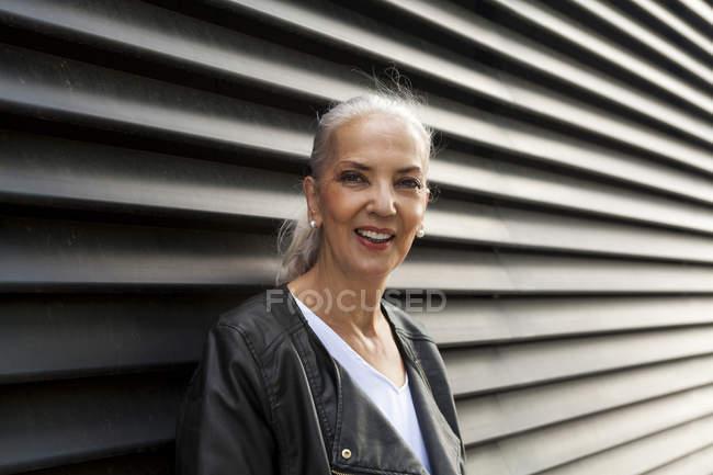 Retrato de mujer madura sonriente frente a la pared negra - foto de stock