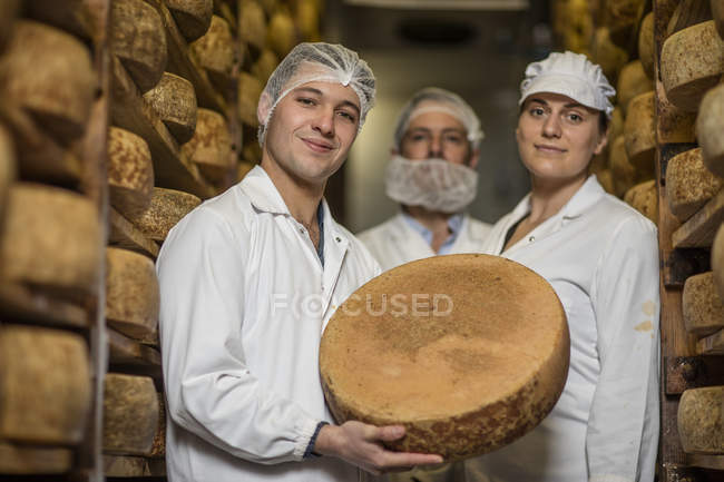 Trabajadores de la fábrica de quesos orgullosamente sostiene pan de queso - foto de stock